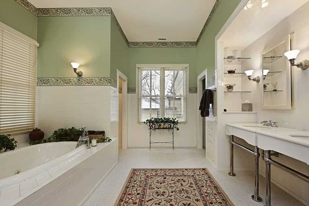 Calming bathroom with green walls lined by leafy wallpapers. It has a vintage rug over the white hexagon floor tiles, a bathtub and a dual porcelain sink vanity.