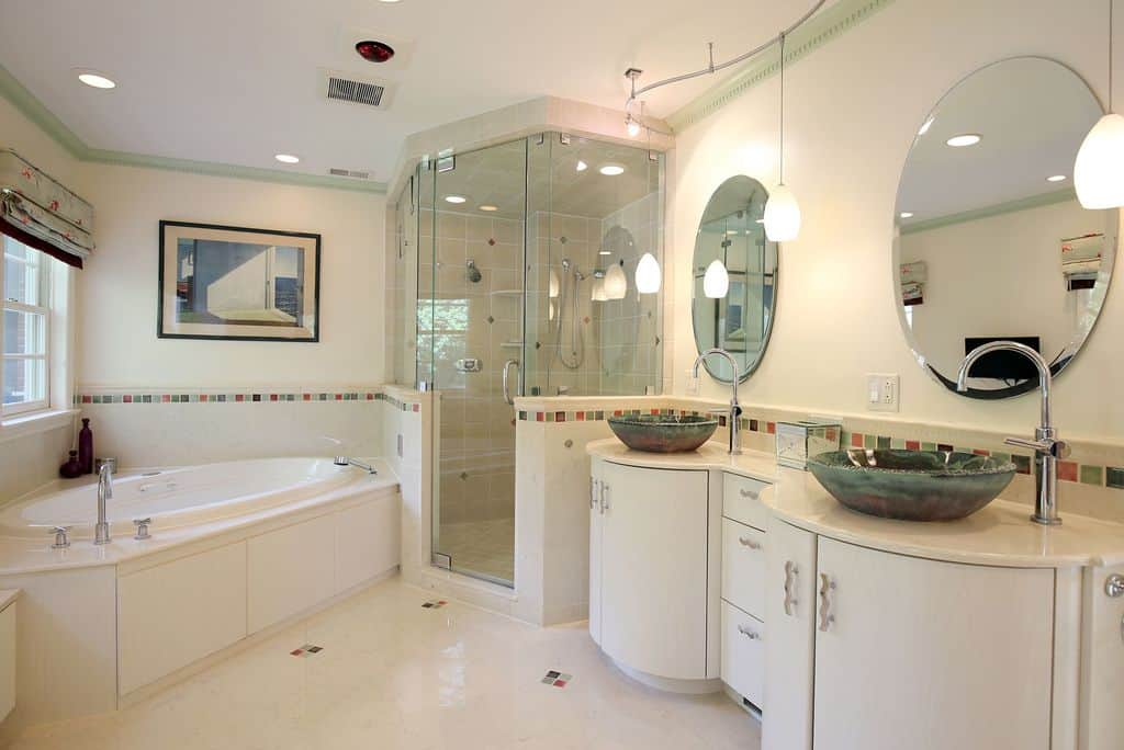 Charming white bathroom with a pop of green features a dual emerald glass vessel sink washstands with round mirrors illuminated by hanging pendant lights. Next to it is the walk-in shower that's adjacent to the white bathtub.