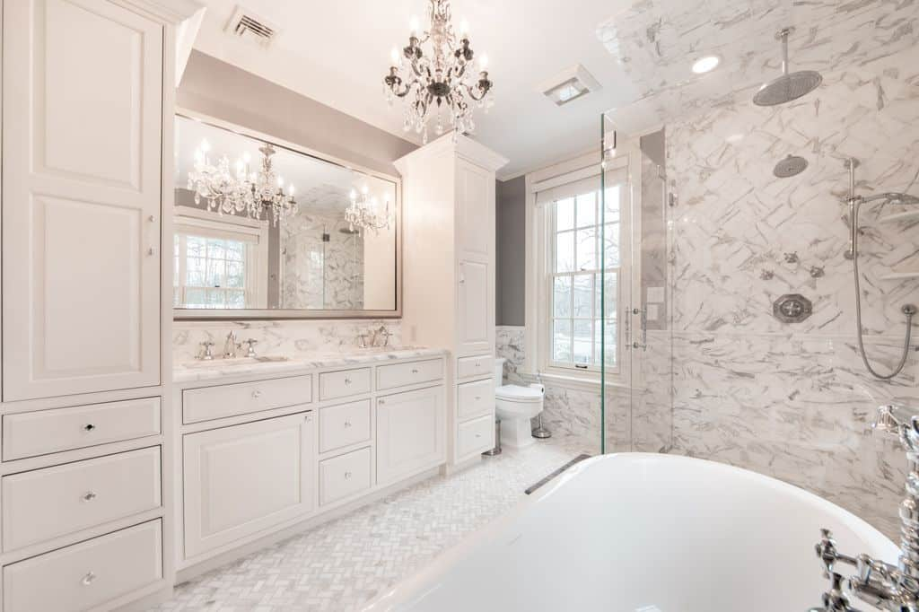 Luxurious white bathroom with a dual sink vanity topped with gray marble and completed with white cabinetry over a herringbone patterned tiles floor. It is illuminated by a fancy crystal chandelier that adds sophistication in this room.