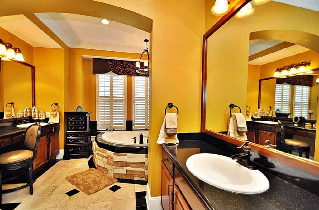Bright yellow bathroom features a corner bathtub along with wooden washstands paired with a black cushioned chair and a small black cabinet.
