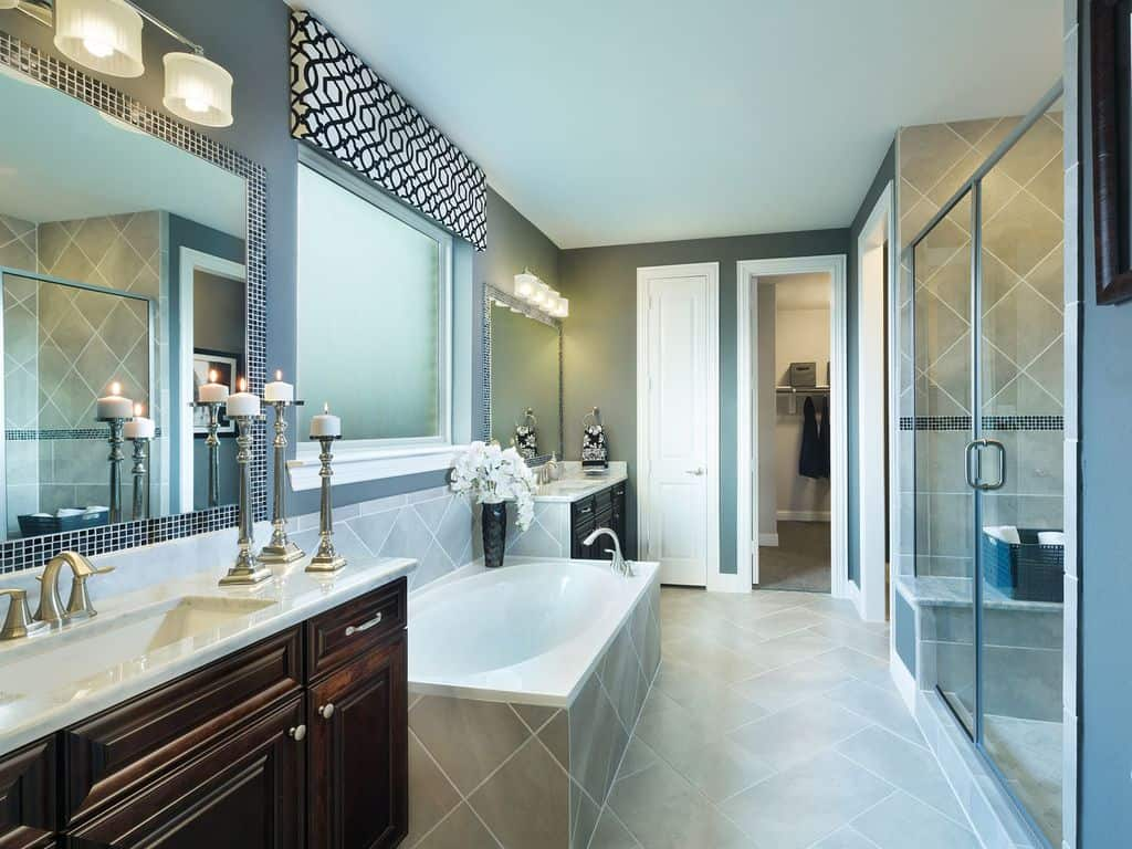 Elegant bathroom with a tub fixed in gray tiles backsplash that matches the floor. It also has a wooden sink vanity lighted by candles and a wall sconce mounted above the mirror.