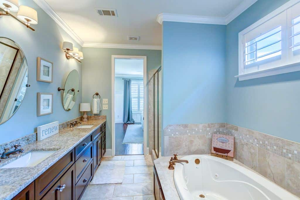 Cool blue bathroom featuring a long dual sink vanity with mirrors and lighted by wall sconces mounted above it. It faces the walk-in shower and bathtub that's fixed to a marble backsplash.