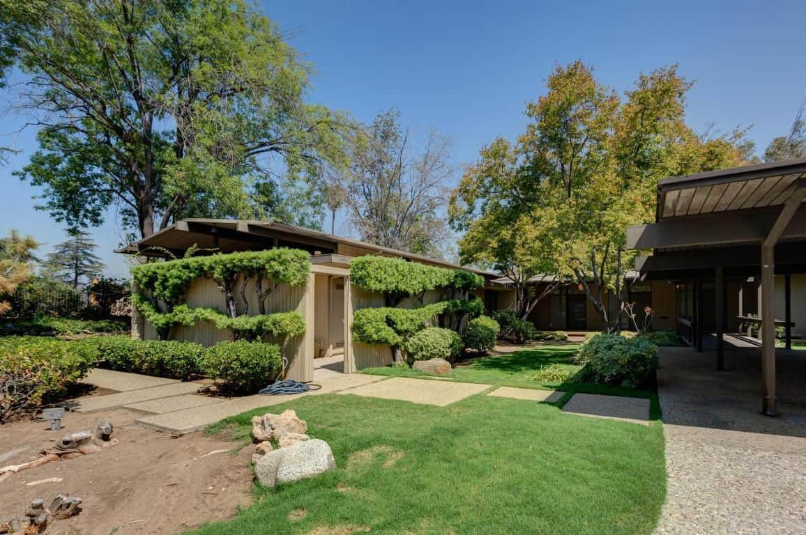 The garden creates a Zen atmosphere with its manicured lawn and well-trimmed hedges.