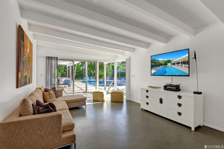 This living room offers a pair of ottomans and an L-shaped sectional facing the white console table and television. It has concrete flooring and glass sliders that open to the patio and the sparkling swimming pool.