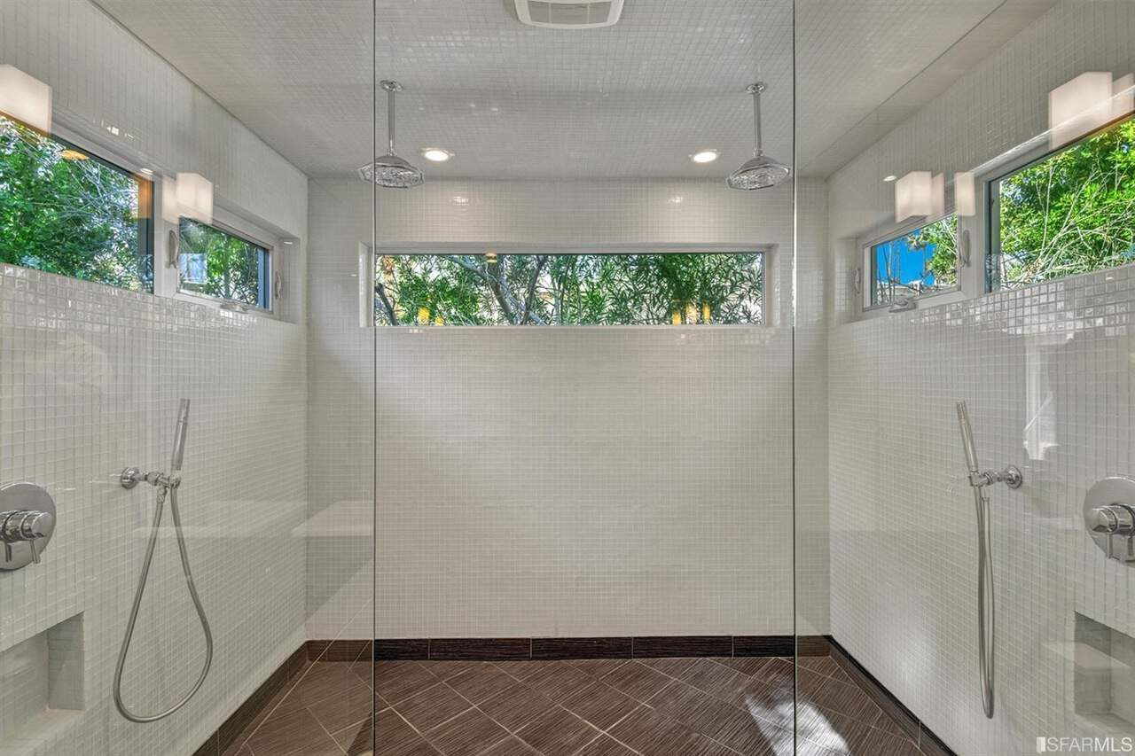 A close up look at this mid-century primary bathroom's large shower room with white tiles walls and brown tiles flooring.
