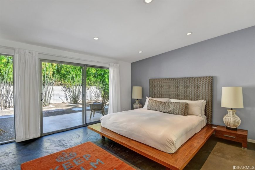 Mid-century modern master bedroom featuring a classy large bed with table lamps on both sides surrounded by white and gray walls.