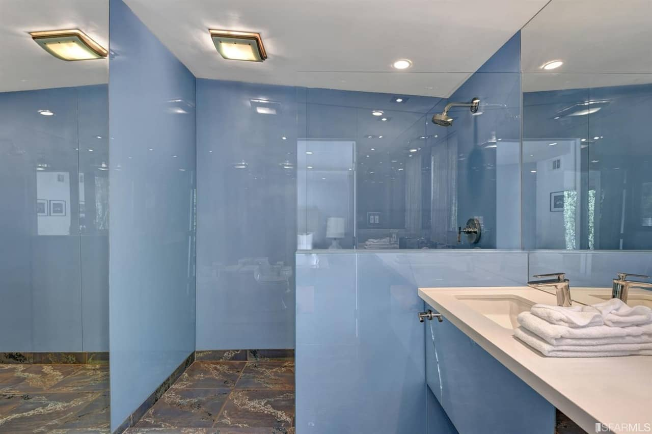 This primary bathroom in mid-century style boasts sky blue walls along with stylish tiles flooring. It also features a shower area and a floating vanity sink.