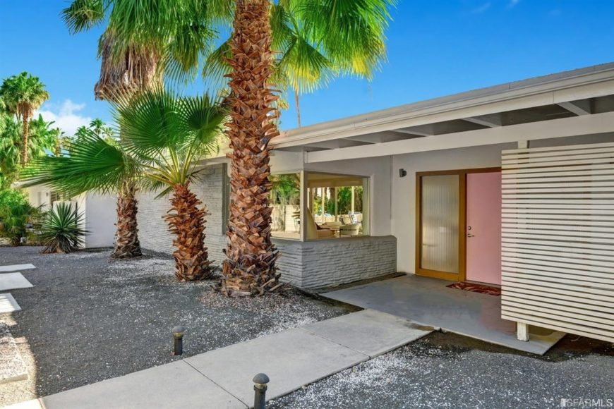 A row of palm trees in the front yard set the tone for this exclusive Palm Springs paradise.
