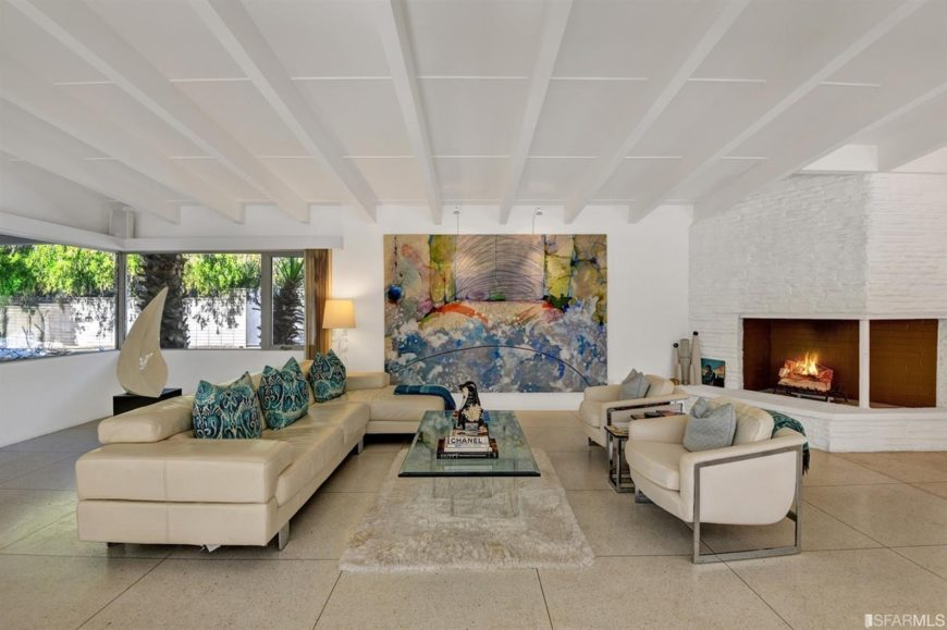 Mid-century living room decorated with a huge abstract canvas mounted on the white wall. It has a corner fireplace and glass top coffee table that sits in between beige leather seats accented with gray and patterned pillows.