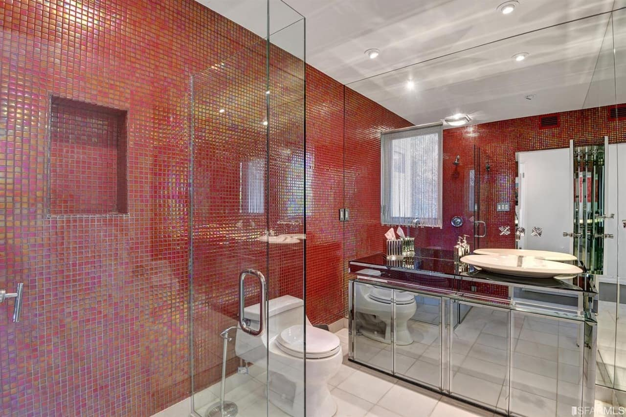 Primary bathroom with red tiny tiles walls. It also features a vessel sink and white tiles flooring, along with a walk-in shower room.
