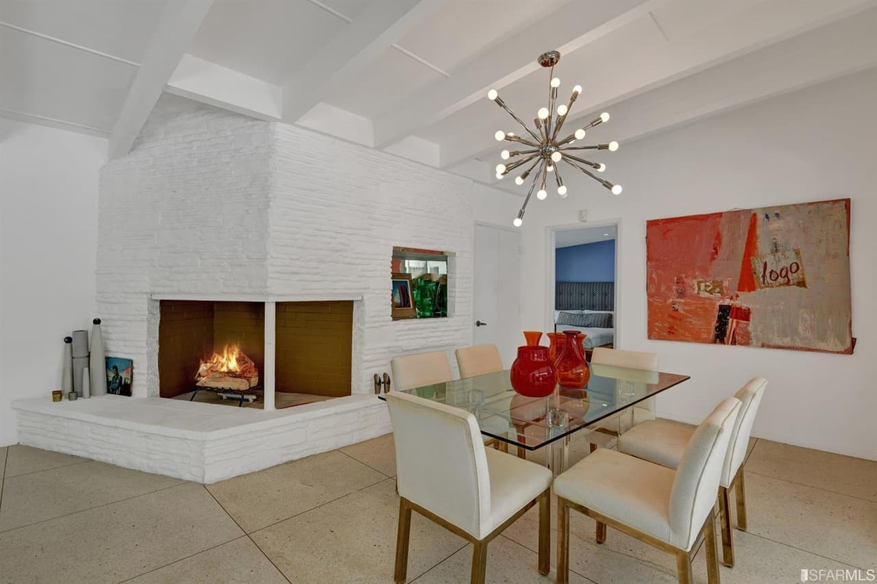 A mid-century style dining room with a glass top rectangle table and classy chairs lighted by a charming ceiling lighting. There's a fireplace on the side to keep the place warm.