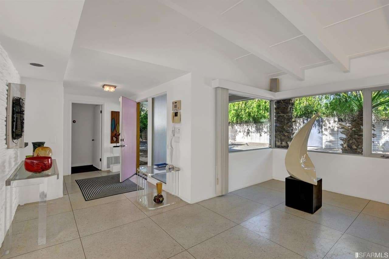 Mid-century home with a spacious entry, featuring large tiles floors and white walls matching the white ceiling.