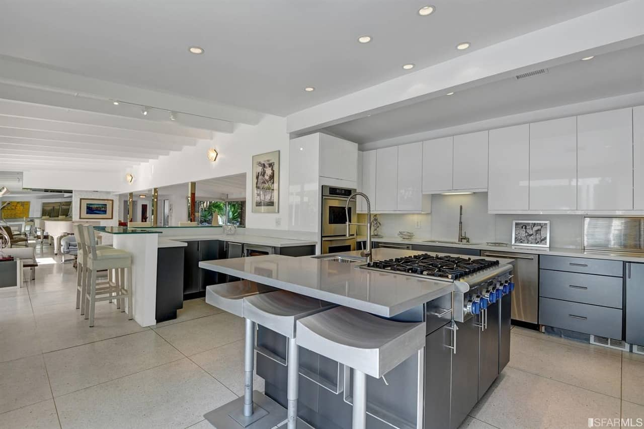 Large kitchen area with modern kitchen counters and center island with a breakfast bar. There's a separate breakfast bar with a glass counter on the side.