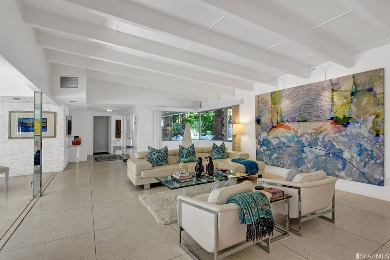White living room with a very attractive large wall decor. The home boasts large tiles floors and a ceiling with beams.