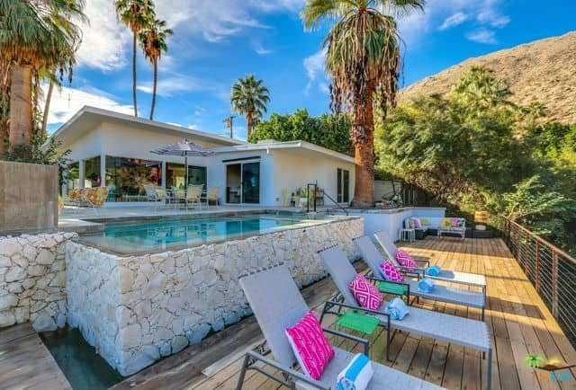 A Mid-century modern house boasting an infinity pool and multiple sitting lounges on the deck.