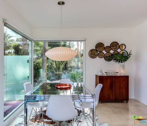 Dining room with glass walls, glass table for four, stylish white plastic chairs, pendant lighting, and tiled floors.