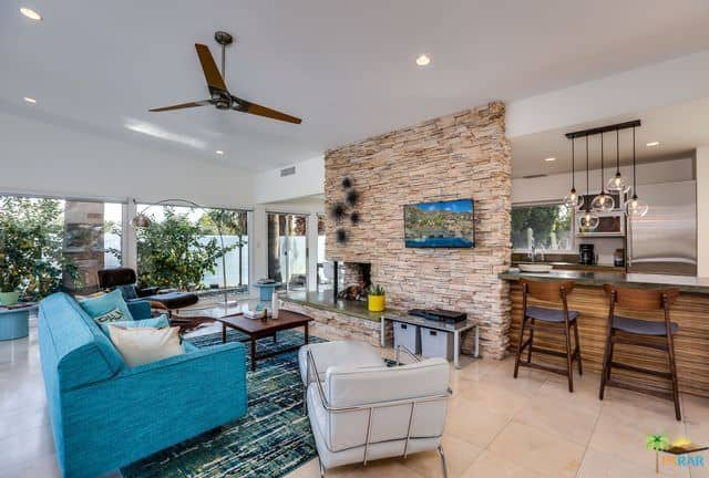 Mid-century modern living room features a blue sofa and comfy recliners facing the fireplace and television mounted on the stone brick pillar. It is attached with a wooden breakfast bar that's paired with counter chairs.