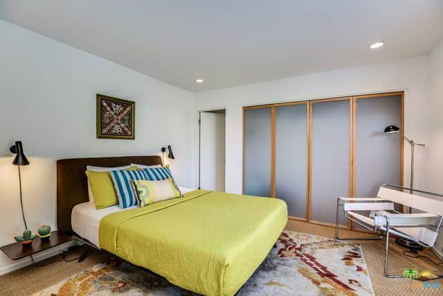 Mid-century modern primary bedroom with a cozy bed set on the carpet flooring topped by a stylish rug.