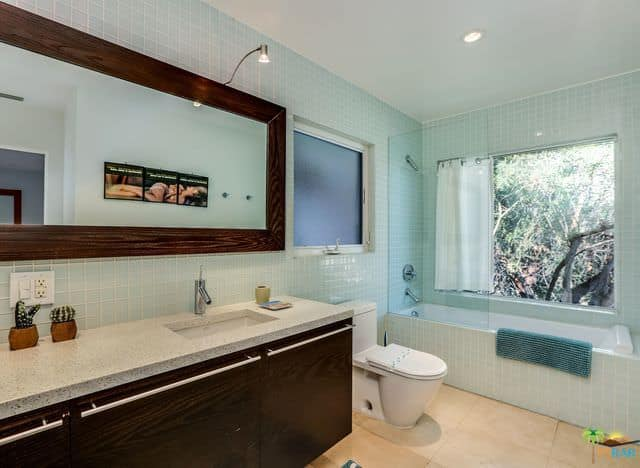 Mid-century primary bathroom featuring lovely tiles walls and floors, along with a drop-in tub by the window.