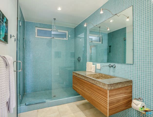 A primary bathroom in mid-century style featuring green tiles walls surrounding the floating vanity sink and the walk-in shower room.