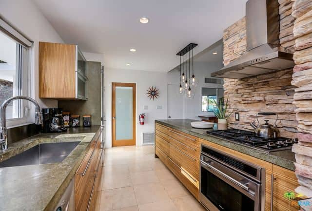 Galley kitchen with textured brick walls on one side, wooden custom cabinets, grouped pendant lights, and tiled floors.