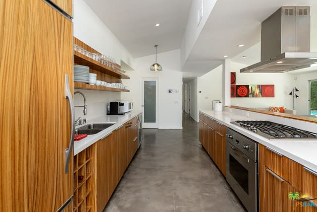 Galley kitchen with rustic wooden cabinets, stainless steel appliances, white countertops, floating wooden shelves, and a combination of pendant and recessed lighting.