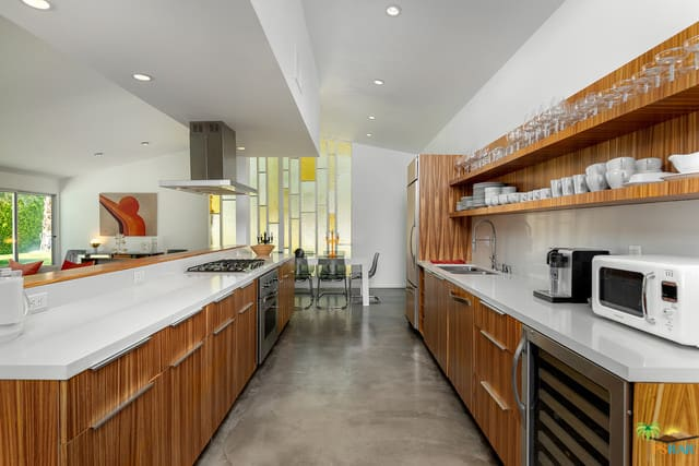 Simple galley kitchen with wooden cabinets, stainless steel appliances, hanging wooden shelves, and recessed lighting.