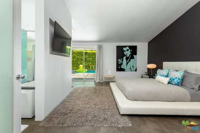 Stylish mid-century modern primary bedroom with black and white walls, along with a large bed set on the gray flooring topped by a gray rug.