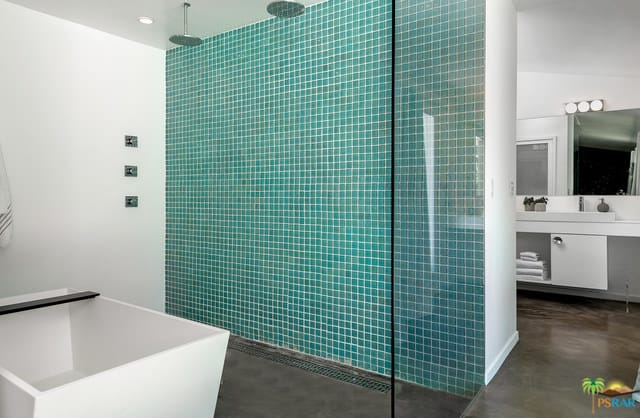 A mid-century primary bathroom featuring a stylish blue tiles wall on the open shower area along with a white freestanding tub.