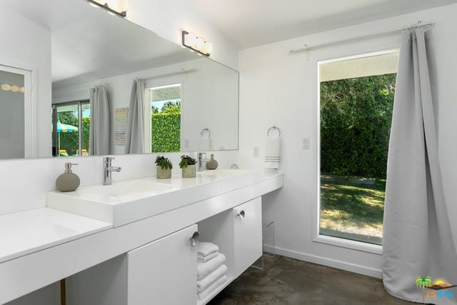 A master bathroom in mid-century style featuring white walls and a white floating vanity sink counter with two large vessel sinks.