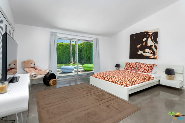 This mid-century modern master bedroom boasts gray flooring and white walls, along with a white shed ceiling.