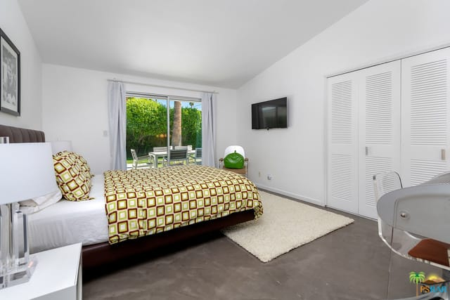 Mid-century modern primary bedroom boasting a large bed set on the gray carpet flooring topped by a rug. The room also has a doorway leading to the home's outdoor area.