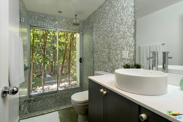 A mid-century primary bathroom featuring stylish tiles walls along with a sink counter with a vessel sink.