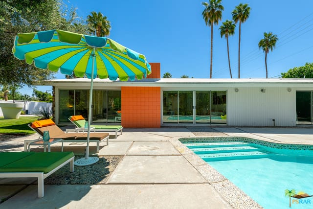 A sprawling bungalow-style mid-century house with a custom outdoor pool and a manicured lawn garden area.