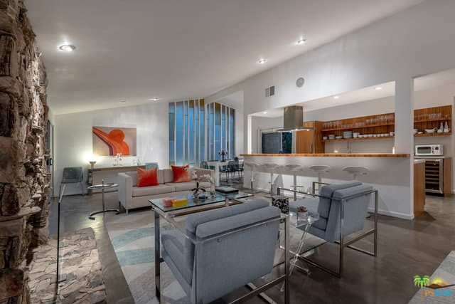 The tall ceiling makes the interior look spacious. The home offers a great room with modern living set, a bar area and a rectangular dining set.