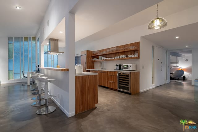 Galley kitchen with rustic wooden cabinets, stainless steel appliances, breakfast island, floating wooden shelves, and a combination of pendant and recessed lighting.