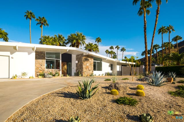 A mid-century bungalow-style house featuring a private oasis-like backyard.