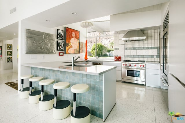 Sleek white kitchen with stainless steel appliances, breakfast island, white tiled floors, brought to life by interesting wall art pieces.
