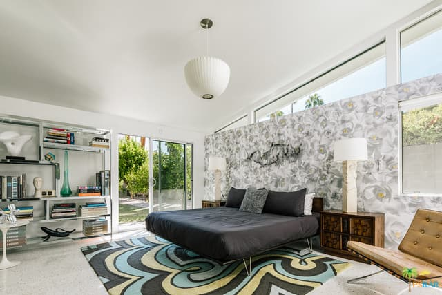 This mid-century modern primary bedroom offers a stylish bed and an attractive wall behind it. The bedroom also has carpet flooring topped by a rug.