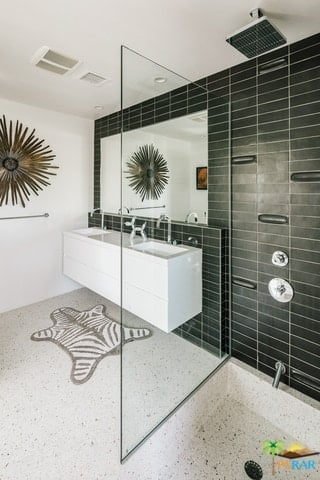 A mid-century primary bathroom featuring black tiles walls and a floating vanity double sink together with the open shower area.