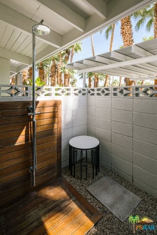 A mid-century master bathroom featuring an open shower room.
