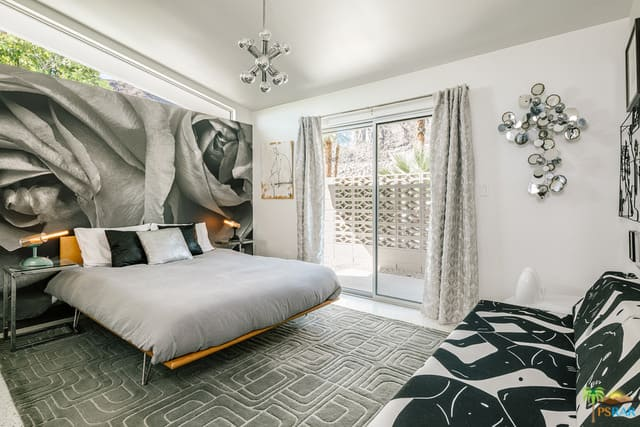 A mid-century modern master bedroom with an artistic wall design behind the bed set on the stylish rug. The room also offers a very stylish couch.
