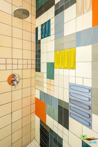 A focused shot at the colorful walls of this primary bathroom in mid-century style.