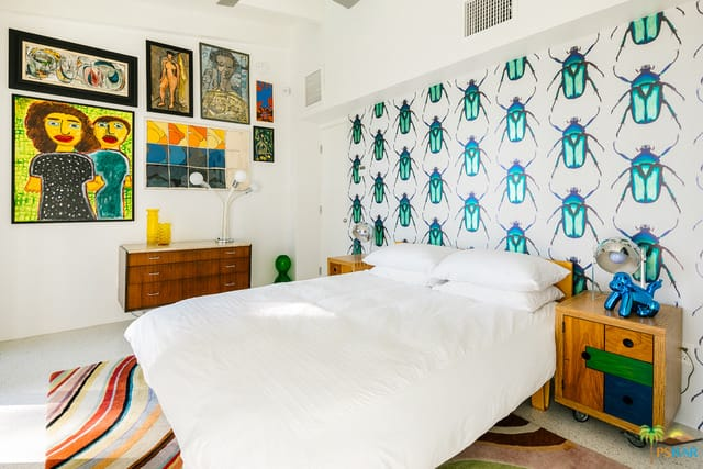 A mid-century modern primary bedroom featuring artistic wall decors and a rug covering the room's flooring.