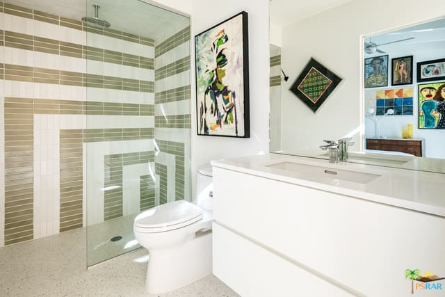 This primary bathroom offers stylish tiles walls surrounding the shower area. The white sink counter shines bright.