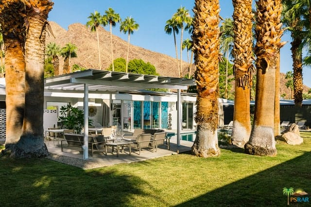 The spacious backyard includes a loggia, a pool, a lawn with palm trees, and a view of the nearby mountains.