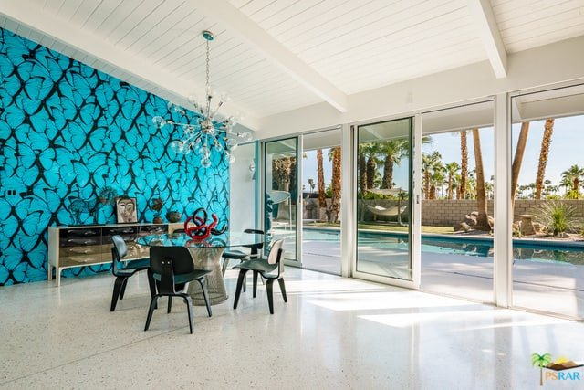 Elegant dining space with an artistic blue wall, direct access to the pool through sliding glass doors, circular glass table for four, and a statement glass pendant light.