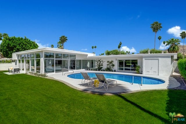 A spacious mid-century house with a sprawling lawn area and a kidney-shaped swimming pool that has a pair of sitting lounges on the side.