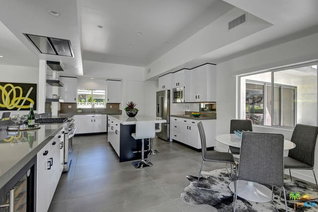 Polished white kitchen with white enamel custom cabinets, breakfast island, stainless steel appliances, and recessed ceiling lights.