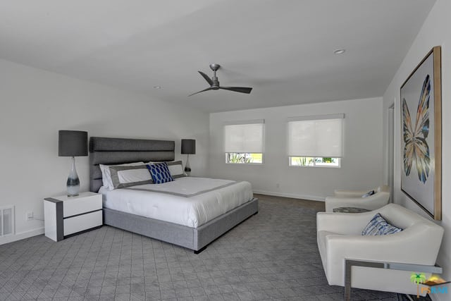 Spacious mid-century modern primary bedroom with white walls and ceiling together with gray carpet floors matching the gray bed frame.